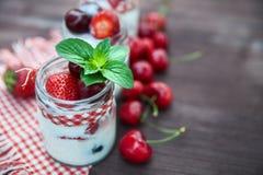 Югурт с вишней и клубниками, квадратом Разбрасывают ягоды голубик и клубник на таблицу Стоковые Изображения