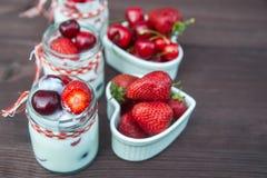 Югурт с вишней и клубниками, квадратом Разбрасывают ягоды голубик и клубник на таблицу Стоковое Изображение RF