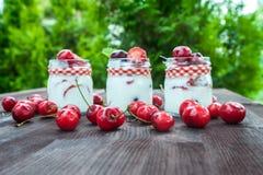 Югурт с вишней и клубниками, квадратом Разбрасывают ягоды голубик и клубник на таблицу Стоковые Фотографии RF