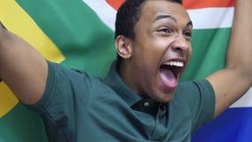 Южно-африканский вентилятор празднуя пока держащ флаг Южной Африки в замедленном движении видеоматериал