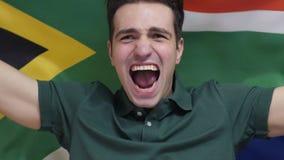 Южно-африканский молодой человек празднует держать флаг Южной Африки в замедленном движении сток-видео