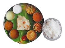 Южные индийские еды плиты на банане листают на белизне Стоковое Изображение