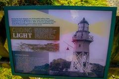 ЮЖНЫЙ ОСТРОВ, НОВАЯ ЗЕЛАНДИЯ 23-ЬЕ МАЯ 2017: Информативный знак маяка на накидке Foulwind, западном побережье юга Стоковое фото RF