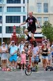 Юнисайкл езды человека во время представления улицы Стоковое Изображение RF
