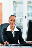 Юрист в офисе сидя на компьютере Стоковые Фото