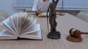 Юрист в рабочем месте рассматривает документы и законодательство, статуэтку Themis со сводным планом акции видеоматериалы