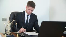 Юрист смотрит через контракт, кладет подпись и печать доллар принципиальной схемы удя крытую работу взгляда наклона места офиса сток-видео