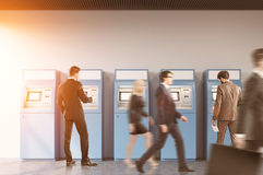 2 люд в зале банка около ATM подвергают механической обработке, тонизированный Стоковое Фото