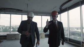 2 люд в костюме и шлеме обсуждают светокопию, высчитывают и связывают с коллегой американская сток-видео