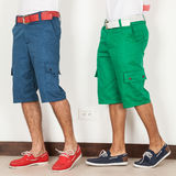2 люд в цветах шортов зеленых и голубых на белой предпосылке Стоковые Изображения RF