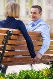 2 люд держа руки пока сидящ на стенде Стоковое Изображение RF