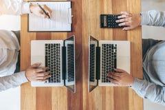 2 люд дела работая на столе офиса и обсуждая использующ Стоковые Изображения RF