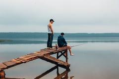 2 люд ждут на деревянном мосте когда рыбы сдержат Стоковое Изображение