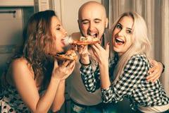 3 люд имея потеху и есть пиццу на партии Стоковая Фотография RF