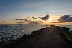 люди наслаждаясь заходом солнца на волнорезе в море с lightho Стоковое Изображение RF