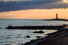 люди наслаждаясь заходом солнца на волнорезе в море с lightho Стоковые Фото