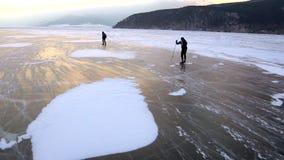 2 люд катаются на коньках на льде замороженного Lake Baikal во время красивого захода солнца сток-видео