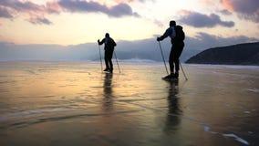 2 люд катаются на коньках на льде замороженного Lake Baikal во время красивого захода солнца видеоматериал
