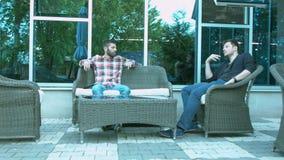 2 люд обсуждают дело сидя на плетеных стульях снаружи в ресторане видеоматериал