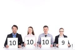 4 люд сидя на таблице и усмехаться. Стоковое Фото
