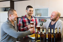 3 люд с пивом на кухне Стоковое Фото