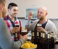3 люд с пивом на кухне Стоковые Фотографии RF