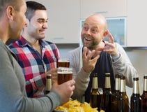 3 люд с пивом на кухне Стоковое Изображение RF
