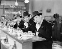3 люд с шляпами есть на счетчике обедающего (все показанные люди более длинные живущие и никакое имущество не существует Поставщи Стоковые Фото