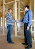 2 люд тряся руки в новом доме строения Стоковые Фото
