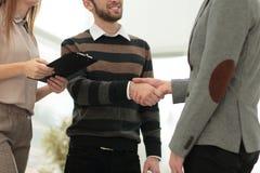 2 люд тряся руки и смотря один другого с улыбкой Стоковая Фотография RF