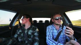2 люд управляя в автомобиле, используя телефон и усмехаться сток-видео