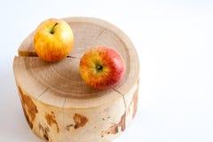 2 яблока лежат на деревянном пне на белой предпосылке с c Стоковые Фотографии RF