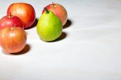 Яблоки и груши на белой деревянной предпосылке Стоковое Фото