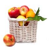Яблоки и tangerines в корзине Стоковые Фото