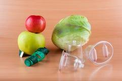 Яблоки, капуста, измеряя лента и masagers кладя на светлую деревянную предпосылку Стоковое Фото
