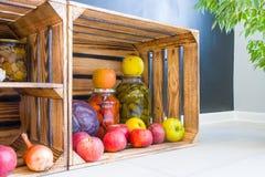 Яблоки, капуста и замаринованные огурцы и томаты в опарниках в деревянной коробке на предпосылке черной стены в кухне Астетически стоковое фото