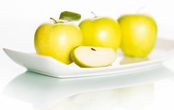 Яблоки на плите изолированной на белой предпосылке. Стоковое фото RF
