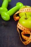 Яблоко, гантели и измеряя лента Стоковые Изображения