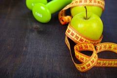 Яблоко, гантели и измеряя лента Стоковое фото RF