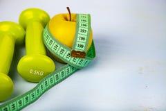 Яблоко, гантели и измеряя лента Стоковое Изображение