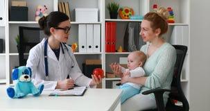 Яблоко доктора молодой женщины предлагая, который нужно быть матерью с младенцем в офисе видеоматериал