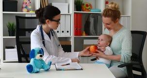 Яблоко доктора молодой женщины предлагая, который нужно быть матерью с младенцем в офисе акции видеоматериалы