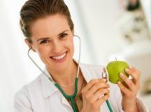 Яблоко женщины врача рассматривая с стетоскопом Стоковое фото RF