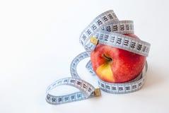 Яблоко и измеряя лента на белой предпосылке диетпитание принципиальной схемы стоковые фотографии rf