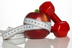 Яблоко и красный цвет покрасили гантели связанный с измеряя лентой Стоковые Изображения RF