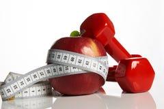 Яблоко и красный цвет покрасили гантели связанный с измеряя лентой Стоковые Фотографии RF