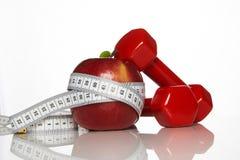 Яблоко и красный цвет покрасили гантели связанный с измеряя лентой Стоковые Изображения