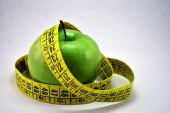 Яблоко и сантиметр на белой предпосылке стоковое изображение