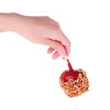 Яблоко карамельки в руке изолированной на белизне Стоковые Фотографии RF