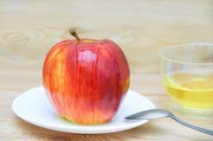 Яблоко на белой плите с ложкой поперченной с медом на деревянной предпосылке стоковая фотография rf
